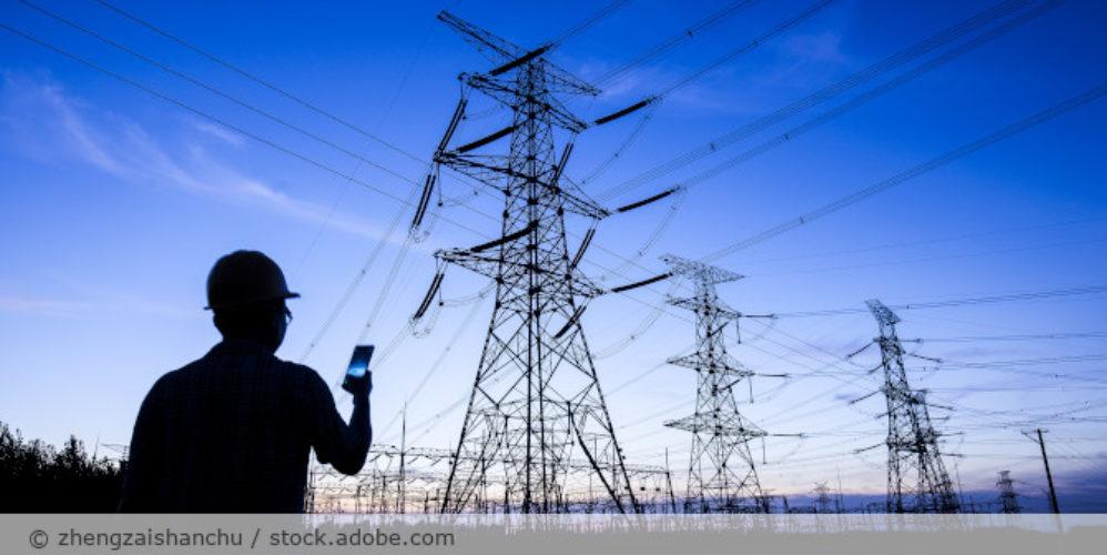 Strommast_Energie_Arbeiter_Handy_stock.adobe.com_225606429