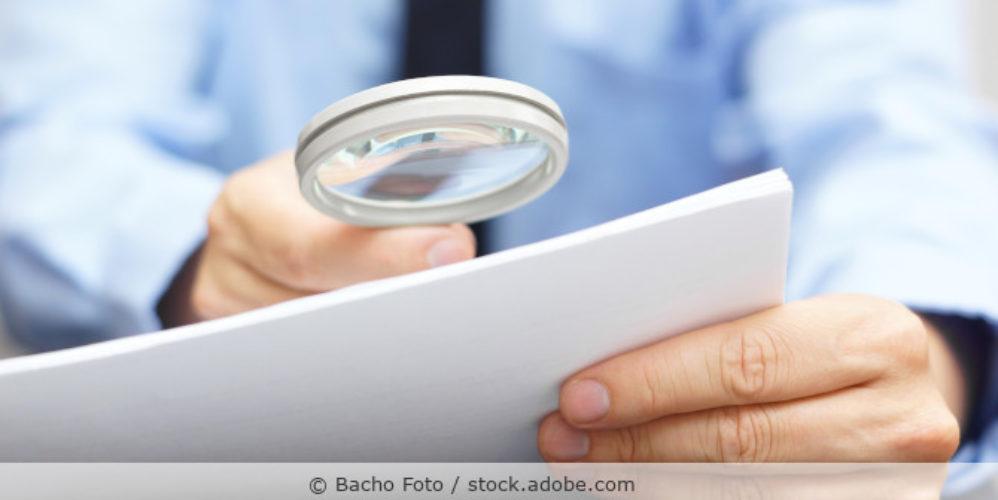 Geschäfstmann untersucht Papier mit einer Lupe