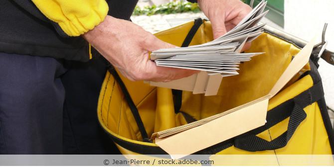 Postbote nimmt mehrere Briefe aus seiner Posttasche