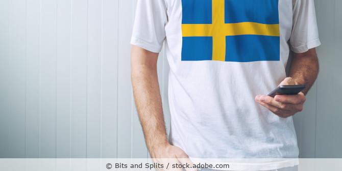 Mann im Schweden-T-Shirt bedient sein Handy
