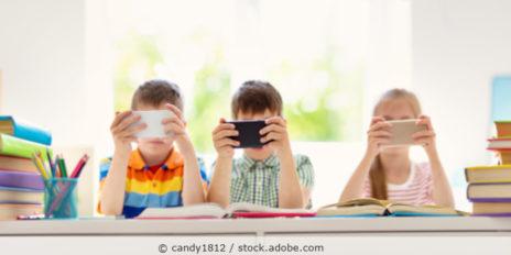 drei Kinder sitzen am Tisch und halten ihr Handy vor die Augen