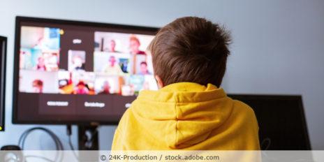 Junge im gelben Hoody sitzt vor einem Computer und nimmt an einer Videokonferenz teil
