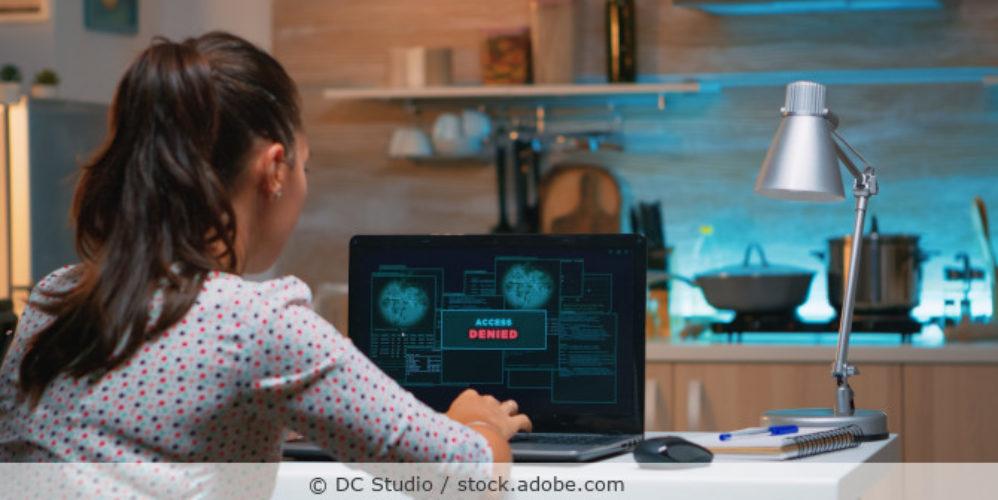 Frau sitzt im Homeoffice vor dem Bildschirm mit der Ansicht Access Denied