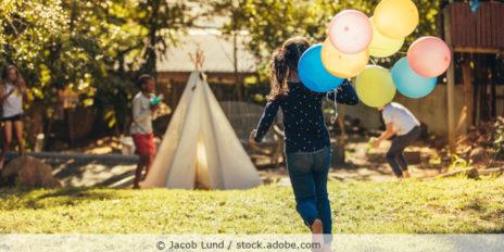 kind mit Luftballons in der Hand läuft im Garten