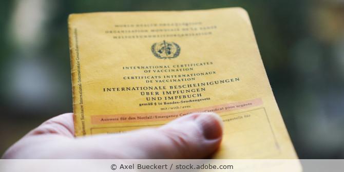 Hand mit gelbem Impfbuch