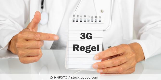 "Artr hält Zettel mit dem Text ""3G-Regel"" hoch"