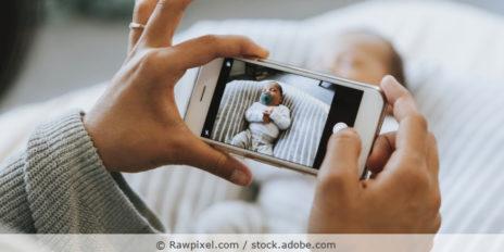 Frau macht ein Foto eines Neugeborenen mit dem Smartphone