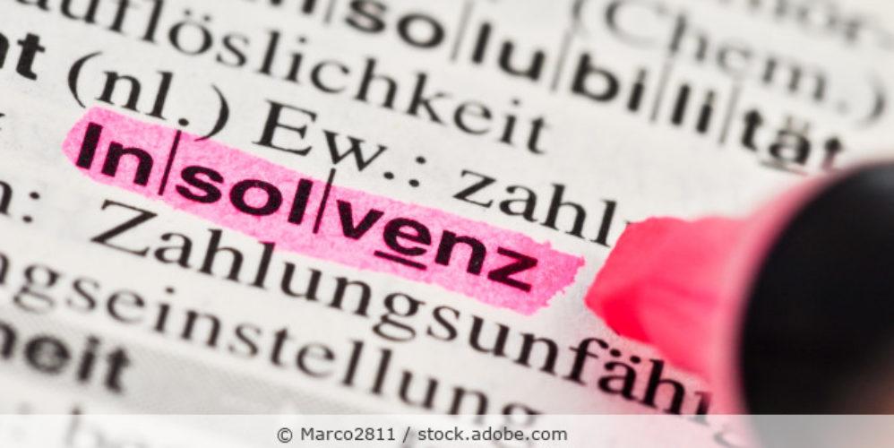 Das Wort Insolvenz mit Textmarker hervorgehoben in einem Buch