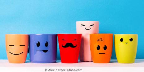 verschiedene Tassen mit Gesichtern vor blauem Hintergrund